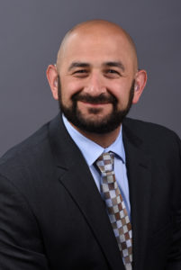A bald white man with a dark, black beard leans slightly and smiles at the camera. He is wearing a dark suit jacket, collared blue shirt, and a tie with brown, gray, and light blue box patterns.